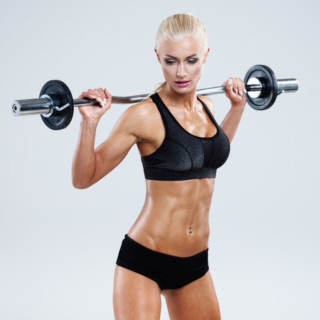 body pump: Athletic woman pumping up muscles with barbell on gray background