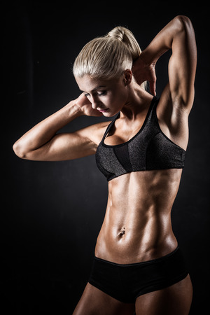 bodybuilder training: Beautiful athletic woman showing muscles on dark background Stock Photo