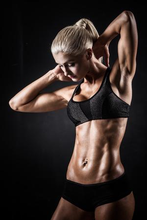 Schöne sportliche Frau zeigt Muskeln auf dunklem Hintergrund