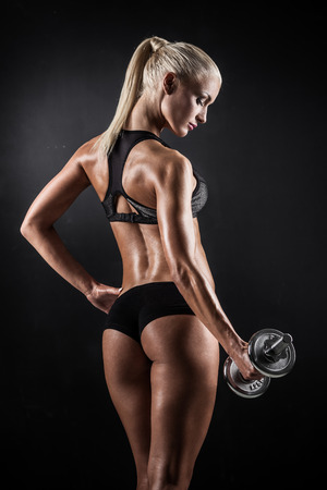 sexy butt: Brutal athletic woman pumping up muscles with dumbbells Stock Photo