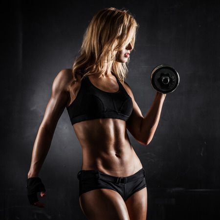 wet body: Brutal athletic woman pumping up muscles with dumbbells Stock Photo