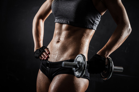 Brutal athletic woman pumping up muscles with dumbbells Standard-Bild