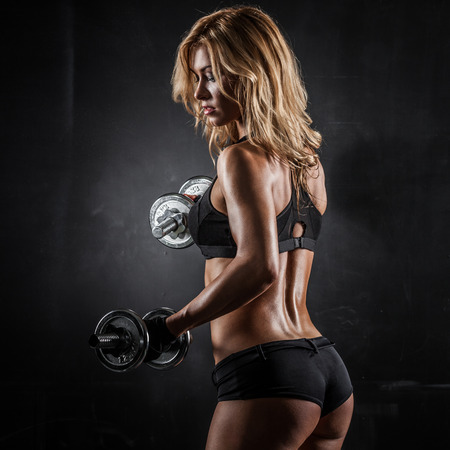 Brutal athletic woman pumping up muscles with dumbbells photo