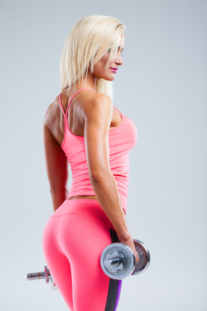 Beautiful fitness model posing with dumbbells on gray background photo