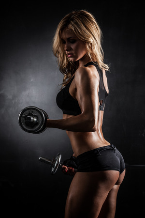 female elbow: Brutal athletic woman pumping up muscles with dumbbells Stock Photo