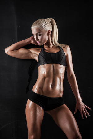Beautiful athletic woman showing muscles on dark background Stock Photo