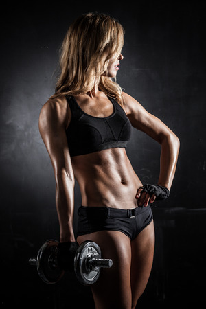 brutal: Brutal athletic woman pumping up muscles with dumbbells Stock Photo