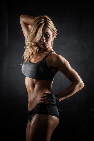 暗い背景に運動の女性示す筋肉を笑顔
