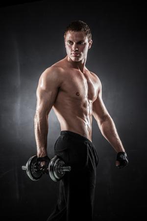 levantar pesas: Hombre atlético hermoso bombeo de músculos con pesas