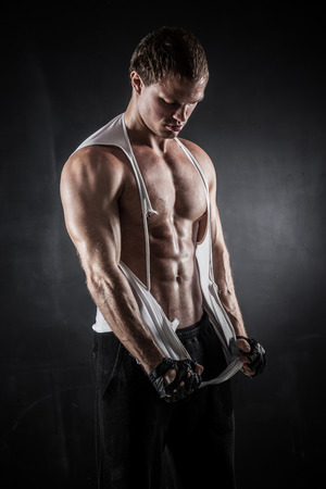 rips: Brutal athletic man rips shirt on dark background