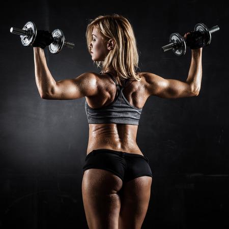 Brutal atletische vrouw oppompen spieren dumbbells Stockfoto