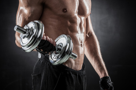 'fit body': Brutal athletic man pumping up muscles with dumbbells