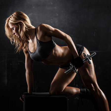 athletic body: Brutal athletic woman pumping up muscles with dumbbells Stock Photo