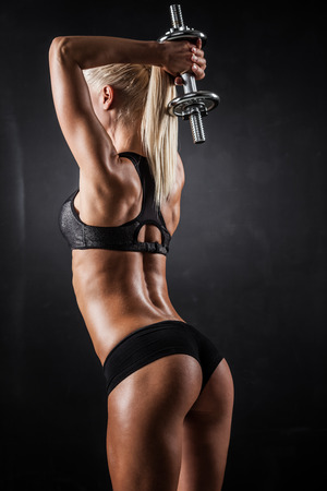human back: Brutal athletic woman pumping up muscles with dumbbells Stock Photo