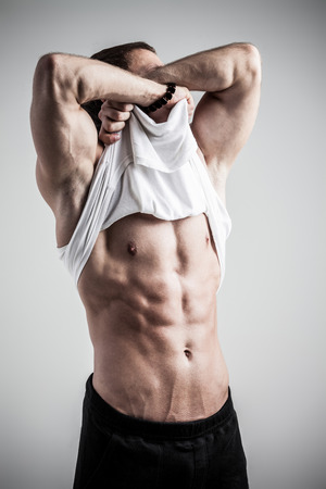Brutal athletic man taking shirt off on gray background photo