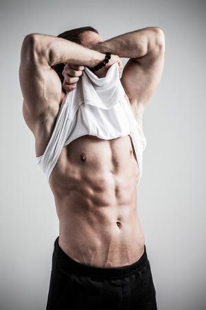 Brutale atletische man nemen shirt uit op een grijze achtergrond Stockfoto