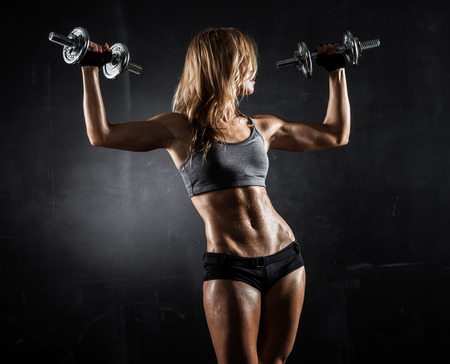 Brutal athletic woman pumping up muscles with dumbbells Archivio Fotografico