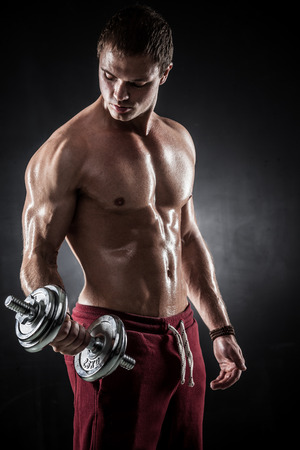 Handsome athletic man pumping up muscles with dumbbells Banque d'images