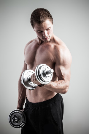 body pump: Young athletic man pumping up muscles with dumbbells Stock Photo