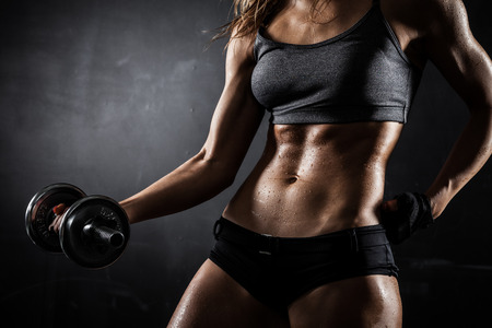 Brutal athletic woman pumping up muscles with dumbbells Zdjęcie Seryjne