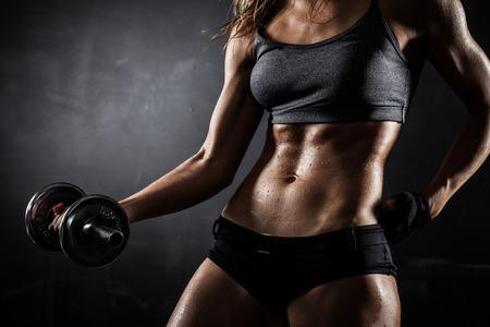 transpiration: Femme athl�tique Brutal pompage des muscles avec des halt�res