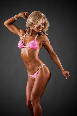body builder: Smiling athletic woman in pink bikini showing muscles on dark  Stock Photo