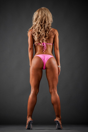 back pack: Athletic woman in pink bikini showing buttocks on dark