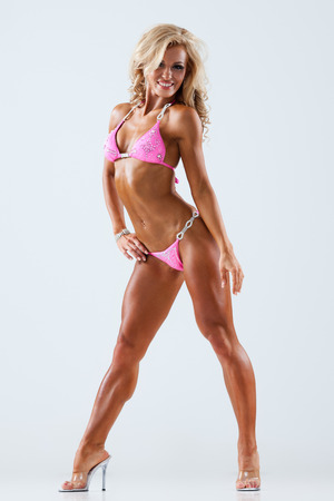 Lächelnde sportliche Frau im rosafarbenen Bikini, der Muskeln zeigt auf grauem