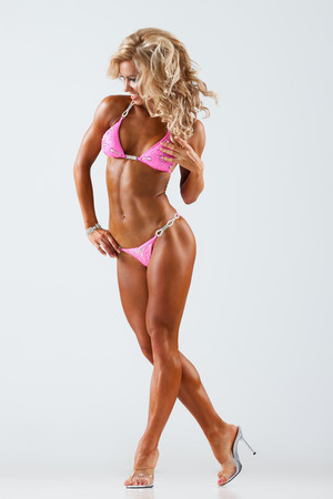 contest: Smiling athletic woman in pink bikini showing muscles on gray background