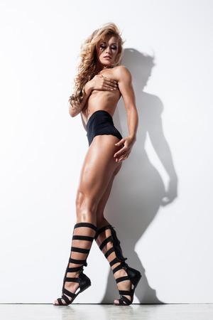 modelos desnudas: Mujer joven atractiva en ropa interior sexy posando cerca de una pared blanca Foto de archivo
