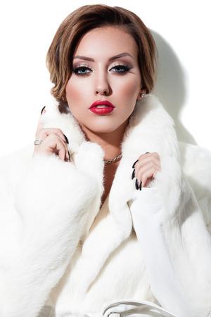 Jeune femme brune en manteau de fourrure blanc posant sur fond blanc