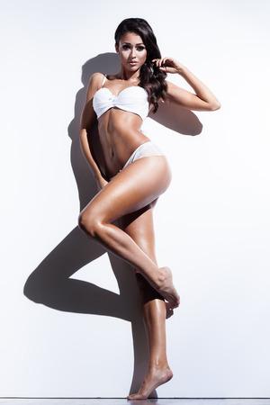 donna che balla: Glamour giovane donna in biancheria sexy posa vicino a un muro bianco