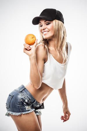 wet clothes: Mujer atl�tica atractiva muestra de color naranja en la ropa mojada en el fondo gris