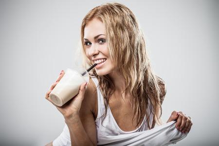wet clothes: Sexy latte atl�tico beber caffe mujer en ropa mojada en el fondo gris