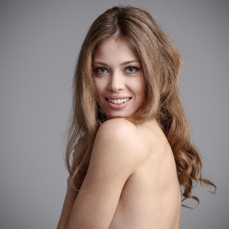 cuerpos desnudos: Señora joven con un cabello hermoso sobre fondo gris Foto de archivo