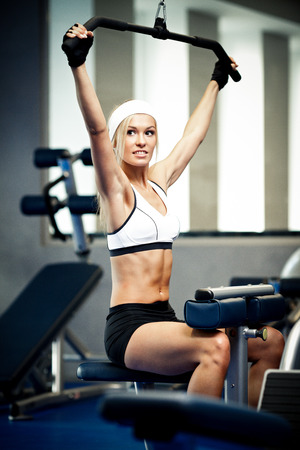 body pump: Smiling athletic woman pumping up muscles in a gym