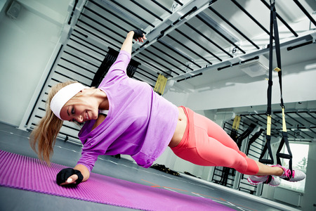 Young woman streching muscles making functional training 写真素材