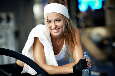 Smiling athletic woman resting on a treadmill