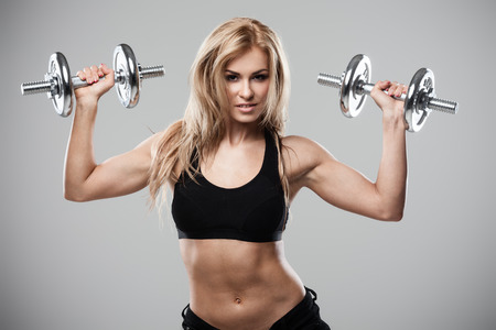 Smiling athletic woman pumping up muscles with dumbbells on gray background photo