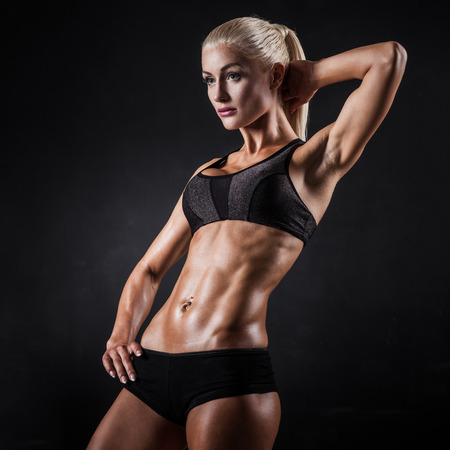 showing muscles: Beautiful athletic woman showing muscles on dark background Stock Photo