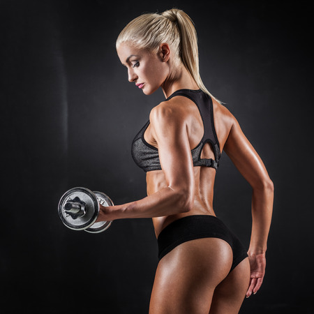 fitness girl: Brutal athletic woman pumping up muscles with dumbbells Stock Photo