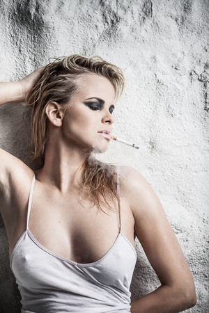 Young lady with wet hair smoking a cigarette posing near a wall photo