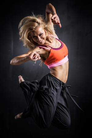 Young woman jumps while making aerobics exercises on gray background Archivio Fotografico