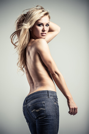 topless jeans: Young topless lady in blue jeans on gray background Stock Photo