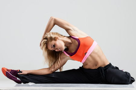 Beautiful fitness model stretches the muscles on a gray background