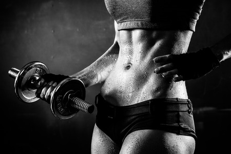 brutal: Brutal athletic woman pumping up muscles with dumbbells in monochrome