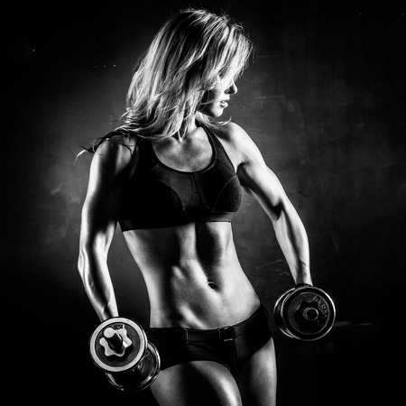 beautiful woman body: Brutal athletic woman pumping up muscles with dumbbells in monochrome