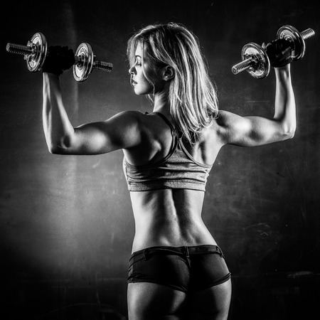 wet body: Brutal athletic woman pumping up muscles with dumbbells in monochrome