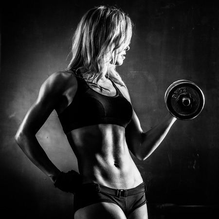 female elbow: Brutal athletic woman pumping up muscles with dumbbells in monochrome
