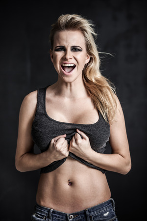 Young blond woman shouting on grey background photo
